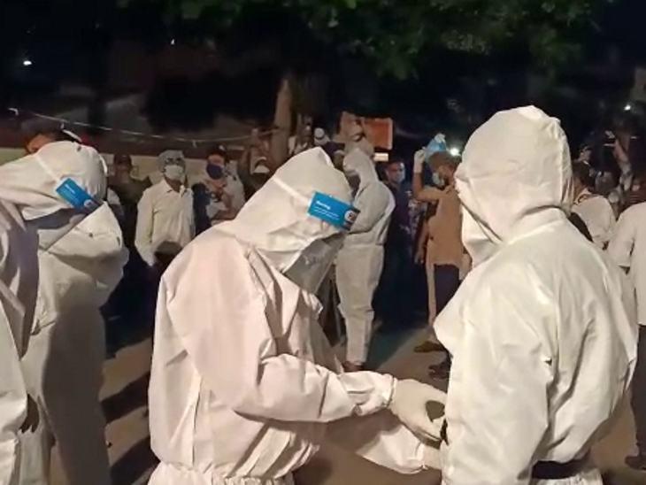 पुलिस के साथ कब्रिस्तान में जाने वालों ने पीपीई किट पहनी।
