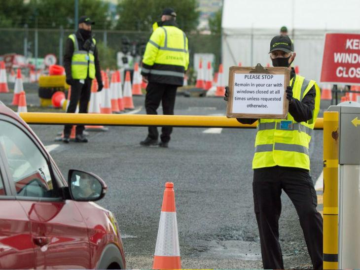 ब्रिटेन में एक टेस्टिंग कैंप के बाहर कार सवार को रूकने के लिए कहते सुरक्षाकर्मी। यहां सरकार ने बुधवार को मौतों का नया आंकड़ा जारी किया है।