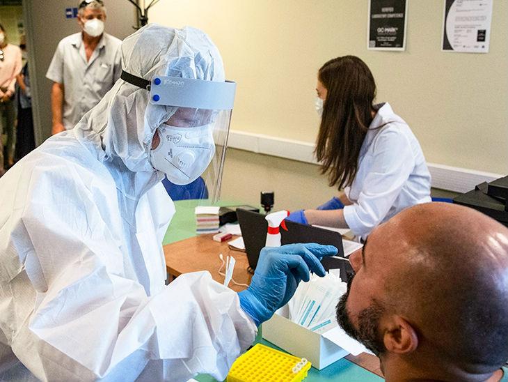 रूस की राजधानी मॉस्को के एक टेस्टिंग सेंटर पर एक व्यक्ति का स्वैब सैंपल लेते स्वास्थ्यकर्मी।