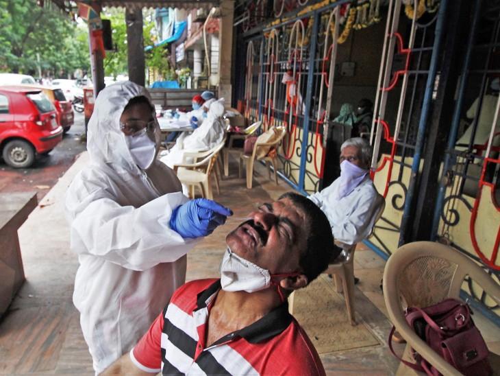 मुंबई के अंधेरी इलाके में एक शख्स का स्वैब टेस्ट के लिए नमूना लेती बीएमसी की महिला स्वास्थ्यकर्मी।