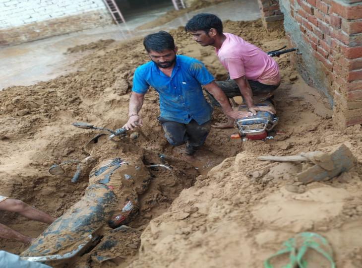 गणेशपुरी कॉलोनी में मिट्टी में दबे वाहनों को निकालते स्थानीय युवक।