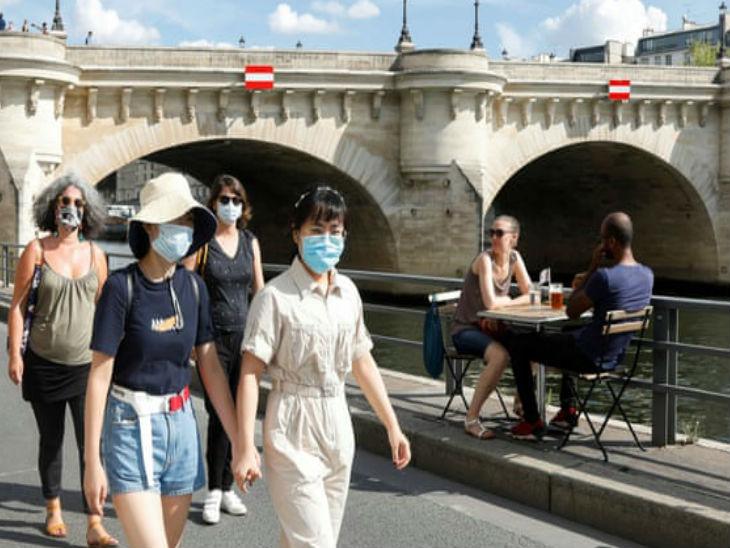 फ्रांस की राजधानी पेरिस में रविवार को मास्क लगाकर टहलते स्थानीय लोग।