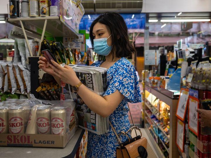 हॉन्गकॉन्ग में रविवार को एक सुपरमार्केट में मास्क लगाकर खरीदारी करती महिला। यहां संक्रमण के मामले कम होने के बावजूद सरकार ने नई पाबंदियों की घोषणा की है।
