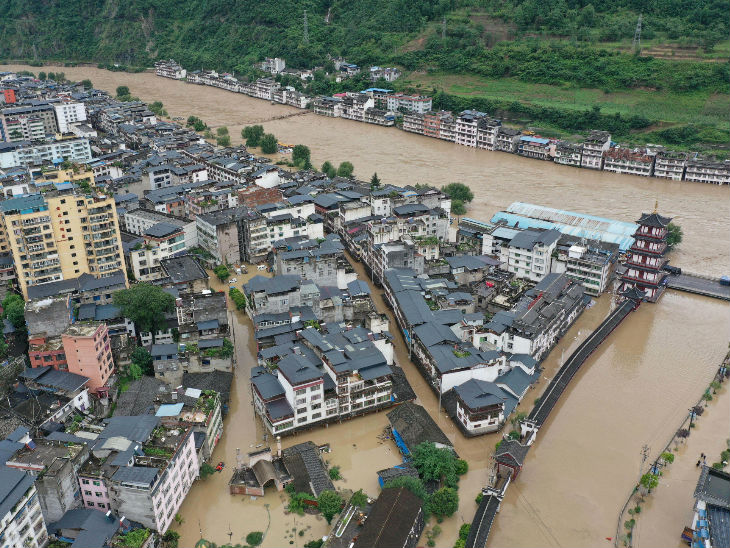 Floodwaters in Bikou town of Longnan city in Gansu province, China. Helicopters have also been deployed to evacuate people.
