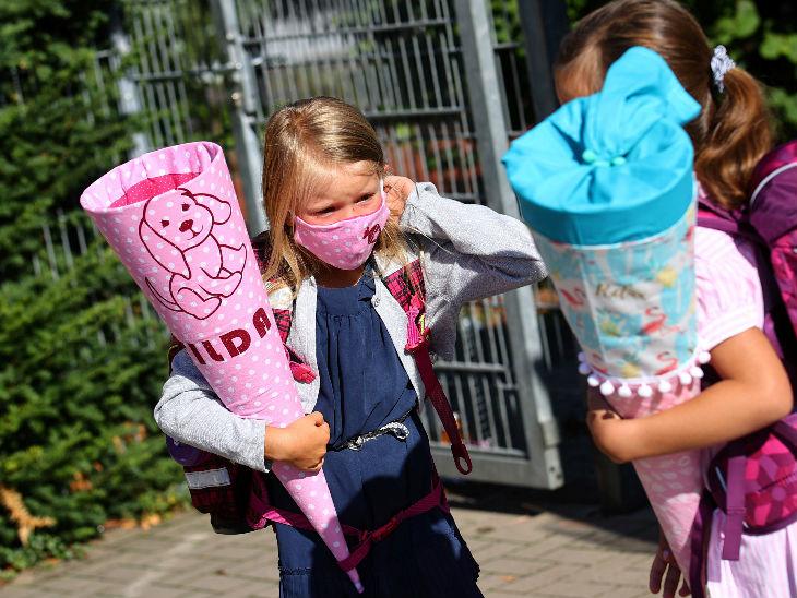 जर्मनी में महामारी के बीच स्कूल खोल दिए गए हैं। फोटो में एक 6 साल की बच्ची अपना मास्क ठीक कर रही है। देश में 2.33 लाख लोग अब तक संक्रमित हो चुके हैं।