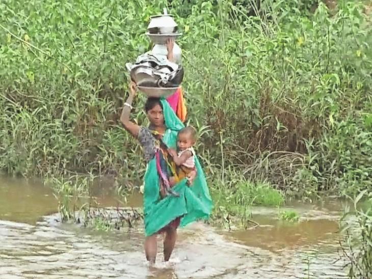 बच्चे को गोद में लेकर नाला पार कर रही महिला