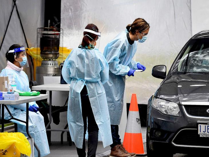 ऑस्ट्रेलिया के मेलबर्न में रविवार को एक कार सवार का टेस्ट करने में जुटे मेडिकल स्टाफ।