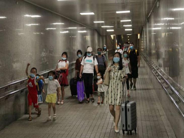 चीन की राजधानी बीजिंग में सोमवार को एक मेट्रो स्टेशन के सबवे में मास्क पहनकर जाते पैसेंजर्स।