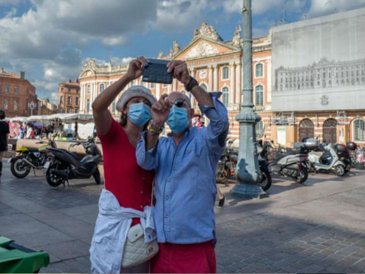 फ्रांस के टोलू में रविवार को मास्क लगाकर सेल्फी लेते टूरिस्ट। सरकार ने यहां सार्वजनिक स्थानों पर मास्क लगाना जरूरी किया है।