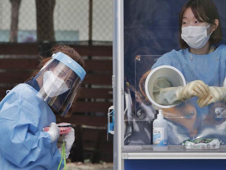 साउथ कोरिया की राजधानी सियोल में सोमवार को एक टेस्टिंग कियोस्क में तैनात मेडिकल स्टाफ।