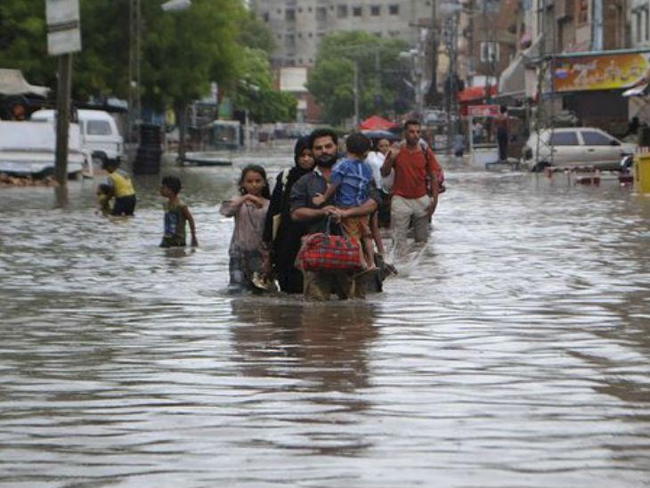 पाकिस्तान के हैदराबाद शहर में एक परिवार घुटनों तक भरा पानी पारकर सुरक्षित जगह की ओर जाता हुआ।