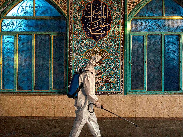इराक के बगदाद शहर में मंगलवार को एक मस्जिद को सैनिटाइज करता कर्मचारी।