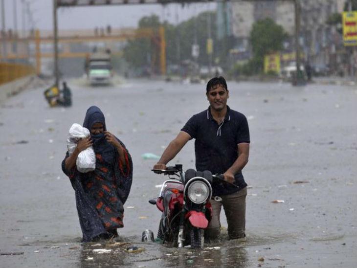 कराची में मंगलवार को एक दंपती अपने दोपहिया वाहन को पानी से डूबी सड़क से ले जाता हुआ।