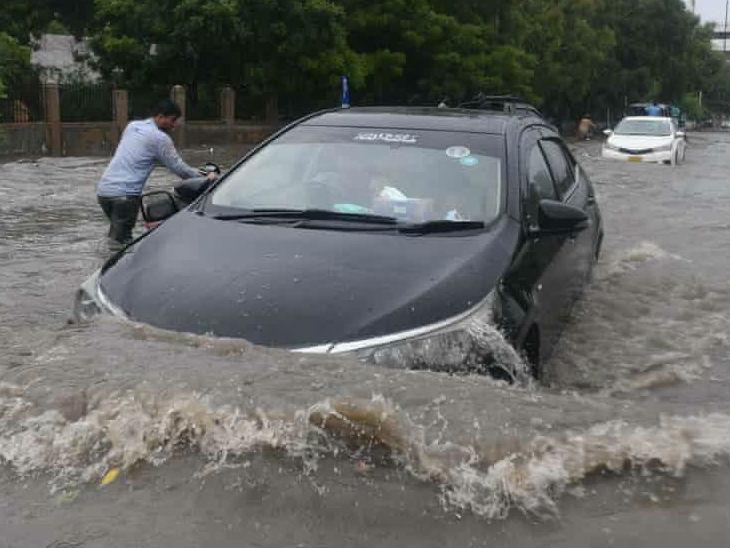 कराची में पानी से भरी सड़क से गुजरती एक कार। शहर के कई प्रमुख सड़कों की ऐसी ही स्थिति है।