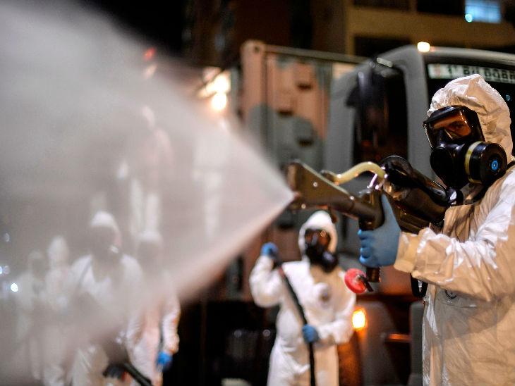 ब्राजील के बेलो होरिजोंटे शहर के एक बाजार में गुरुवार को डिसइनफेक्टेंट का छिड़काव करते सेना के जवान।