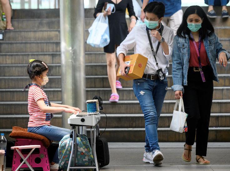 थाईलैंड की राजधानी बैंकॉक में लोग शनिवार को इलेक्ट्रिक कीबोर्ड खेलते हुए एक लड़की के सामने मास्क पहने हुए थे।