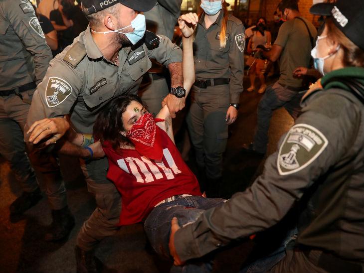 इजराइल के यरूशलम में पीएम बेंजामिन नेतन्याहू के खिलाफ प्रदर्शन करते लोगों को हटाती पुलिस। यहां संक्रमण के चलते लॉकडाउन के नियमों को सख्त किया गया है, लोग इसका विरोध कर रहे हैं।