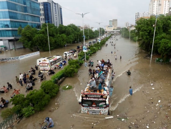 कराची में एक पानी से भरी सड़क पर बस की छत पर बैठकर सफर करते लोग। सोर्स- डॉन
