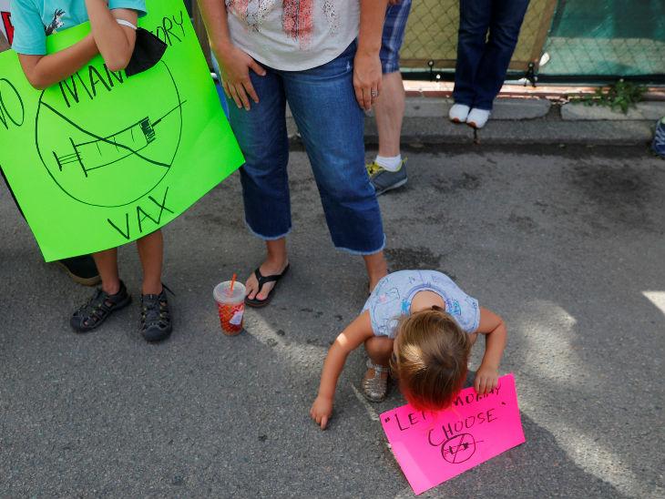 अमेरिका के मैसाच्युसेट्स में गवर्नर के आदेश के खिलाफ प्रदर्शन करता तीन साल का बच्चा और उसके परिजन। यहां 30 साल से कम के सभी स्टूडेंट के लिए फ्लू का टीका लगाना जरूरी कर दिया गया है, इस फैसले का विरोध हो रहा है।