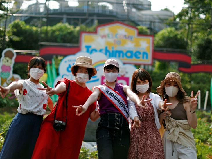 जापान के तोशिमान पार्क में मास्क पहनकर पहुंची युवतियां। महामारी के चलते इस पार्क को 94 सालों में पहली बार बंद किया गया था। अब इसे फिर से खोला गया है।