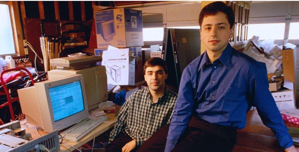 स्टैनफोर्ड यूनिवर्सिटी के अपने कमरे में सर्गेई ब्रिन (नीली शर्ट में) और लैरी पेज। इसी कमरे में पहली बार गूगल का मशहूर सर्च कोड लिखा गया था।