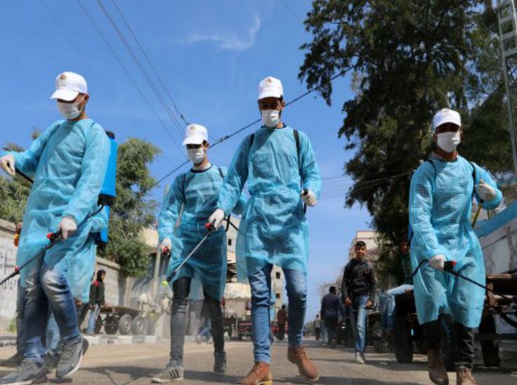 इजराइल के डेर अल-बलाह में एक स्कूल के एंट्रेस गेट के सामने डिसइनफेक्ट का छिड़काव करते सफाई कर्मचारी।