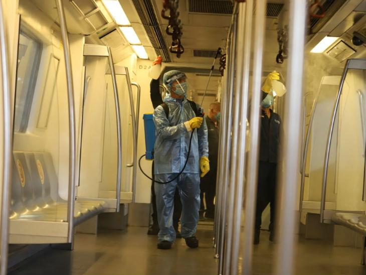 मेट्रो ट्रेन को सैनिटाइज करते कर्मचारी।