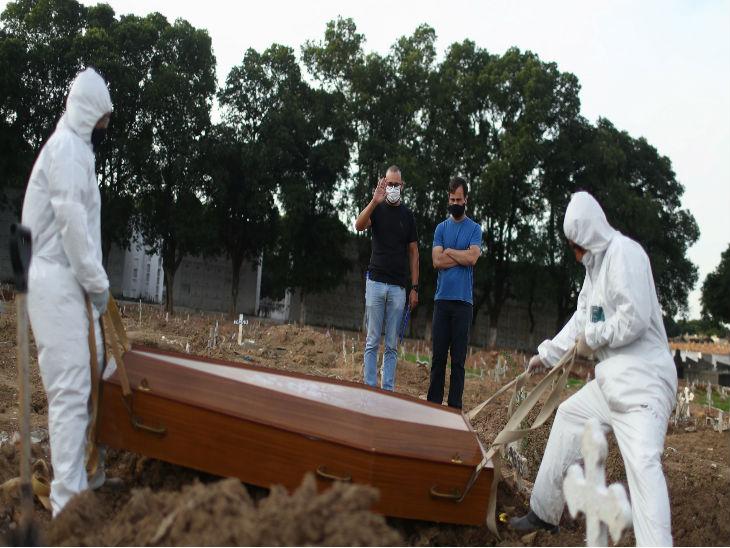 ब्राजील के साओ पाउलो स्थित एक कब्रिस्तान में ताबूत दफनाते कर्मचारी।