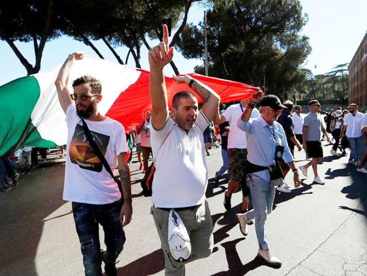 इटली की राजधानी रोम में रविवार को मास्क लगाने के खिलाफ प्रदर्शन करते लोग।