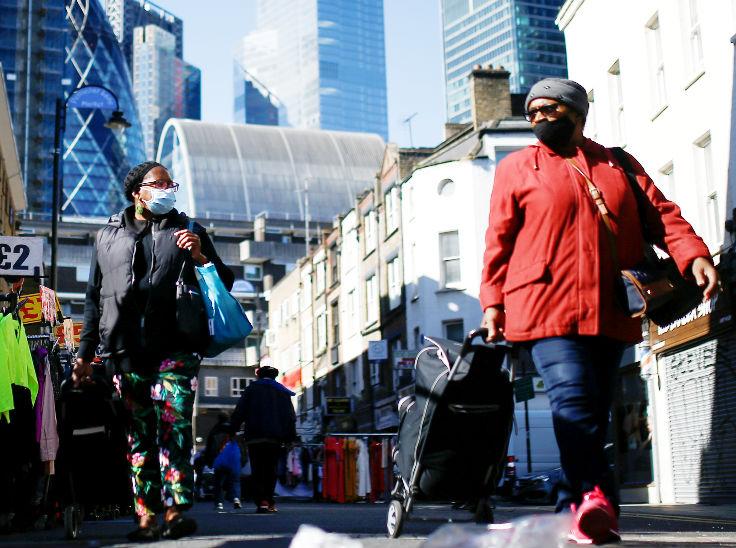 ब्रिटेन की राजधानी लंदन में रविवार को एक बाजार में मास्क पहनकर जाते लोग। देश में बीते कुछ दिनों से नए मामले बढ़ रहे हैं।