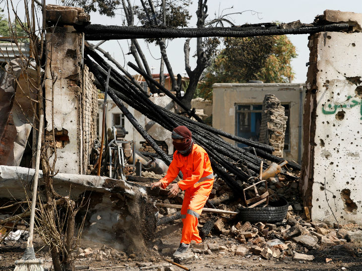 Afghanistan's municipality worker cleaning debris from a damaged shop at the scene.