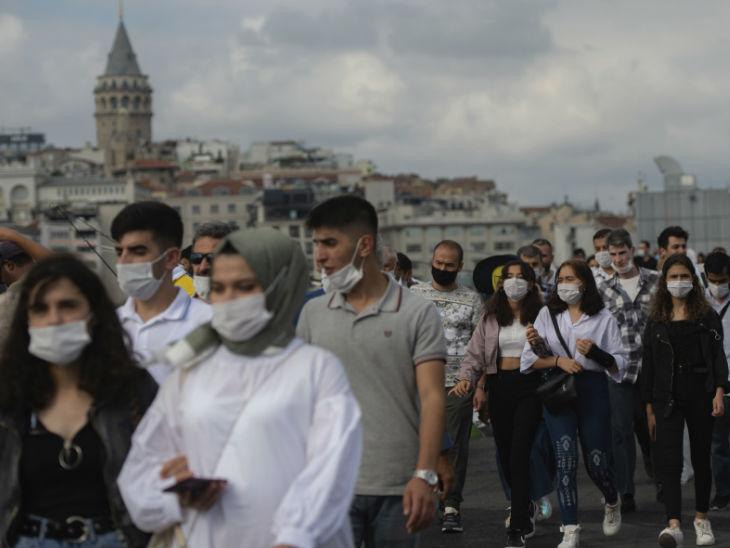 तुर्की के गैलाटा टॉवर में घूमने के दौरान लोग मास्क लगाए नजर आए।