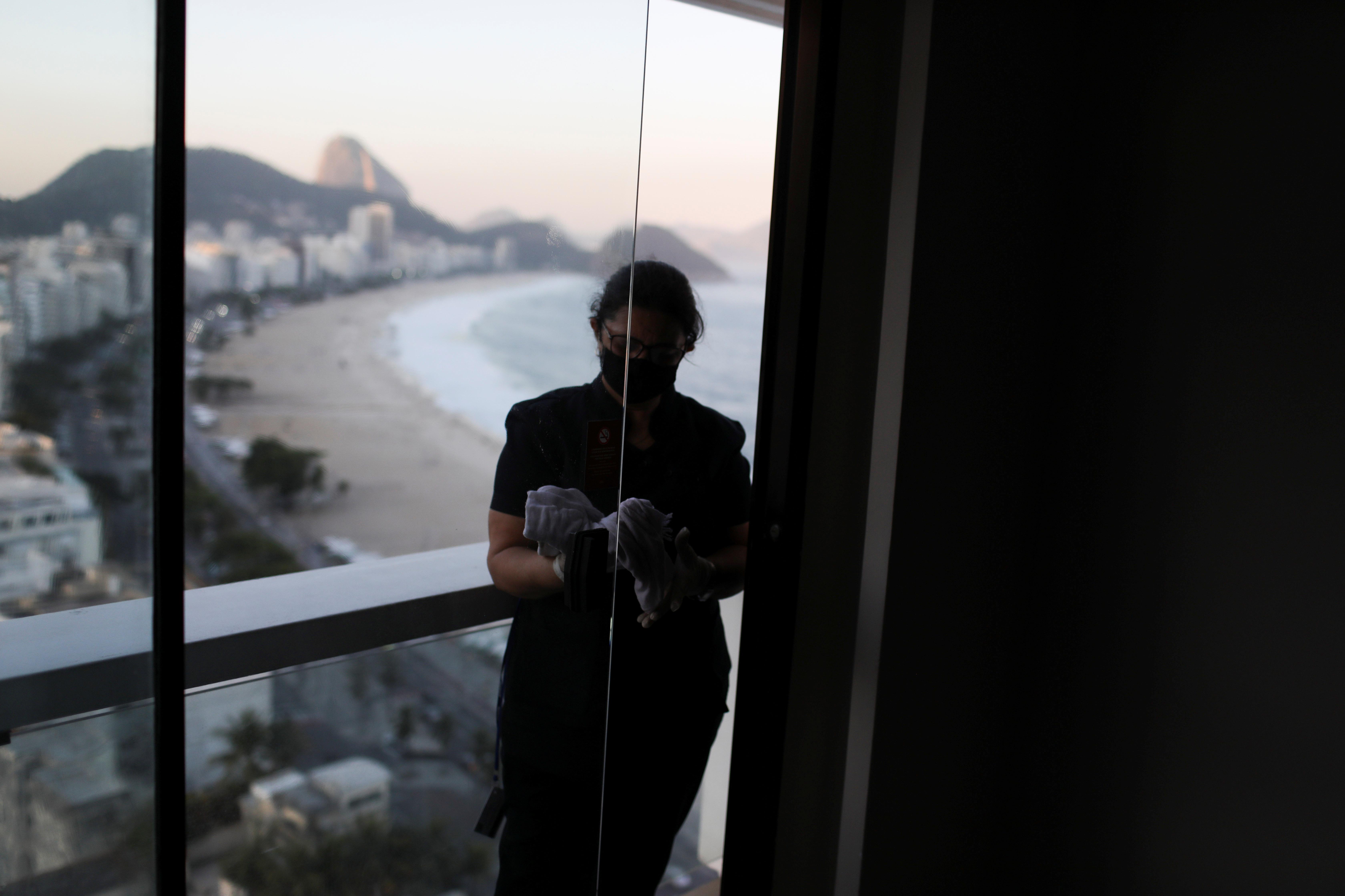 ब्राजील के रियो डि जेनेरियो में एक होटल को सैनिटाइज करती महिला कर्मचारी।