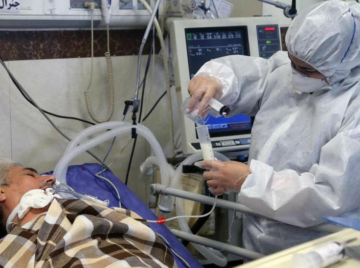 ईरान की राजधानी तेहरान के एक अस्पताल में कोरोना मरीज के इलाज में जुटे डॉक्टर।
