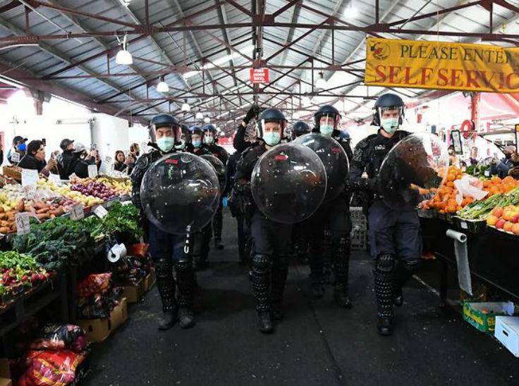ऑस्ट्रेलिया के मेलबर्न स्थित क्वीन विक्टोरिया मार्केट में फल और सब्जियां फेंकते प्रदर्शनकारियों को रोकने पहुंची पुलिस।