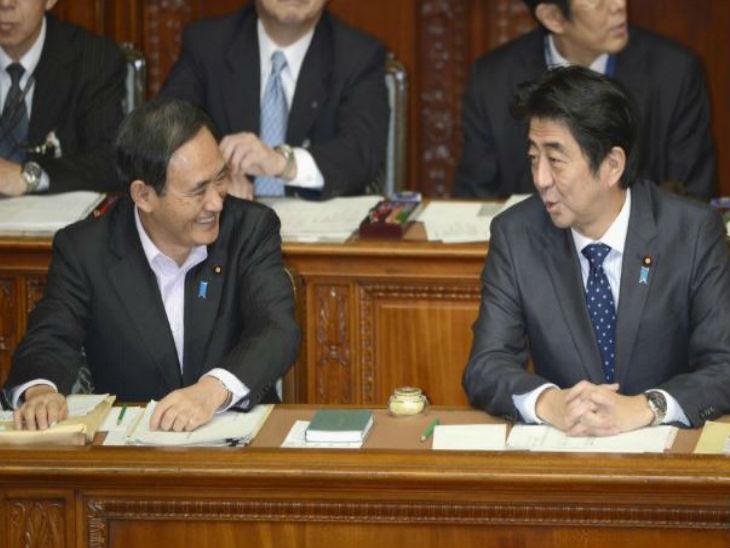 फोटो 2013 की है। इसमें सुगा और पूर्व पीएम आबे संसद सत्र के दौरान एक दूसरे से बात करते नजर आ रहे हैं।
