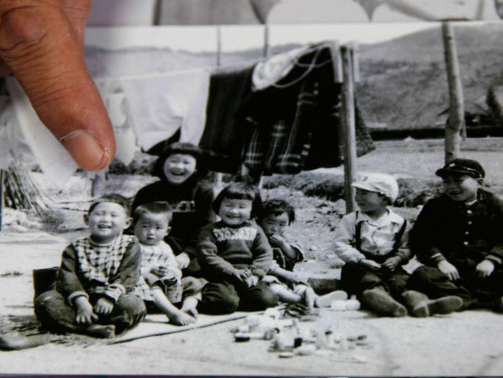 सुगा के बचपन की दोस्त मासाशी यूरी अपने फोटो कलेक्शन में सुगा की बचपन की फोटो दिखाते हुए।