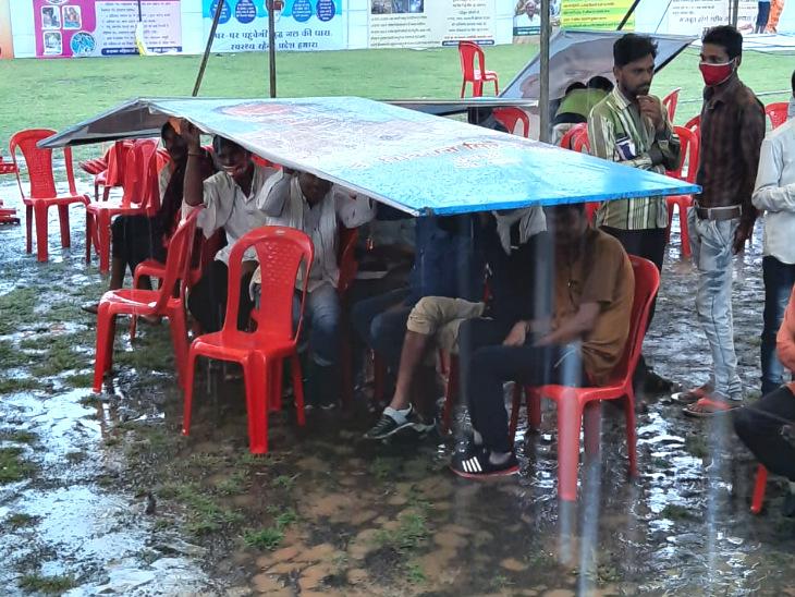 रायसेन के दशहरा मैदान होर्डिंग को छाता बनाकर बारिश से बचने की कोशिश करते लोग।