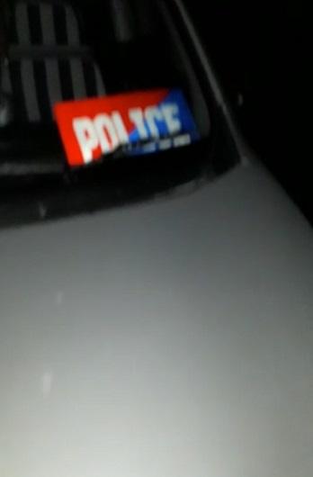 युवक की गाड़ी के शीशे पर पुलिस का नेम प्लेट लगा है।