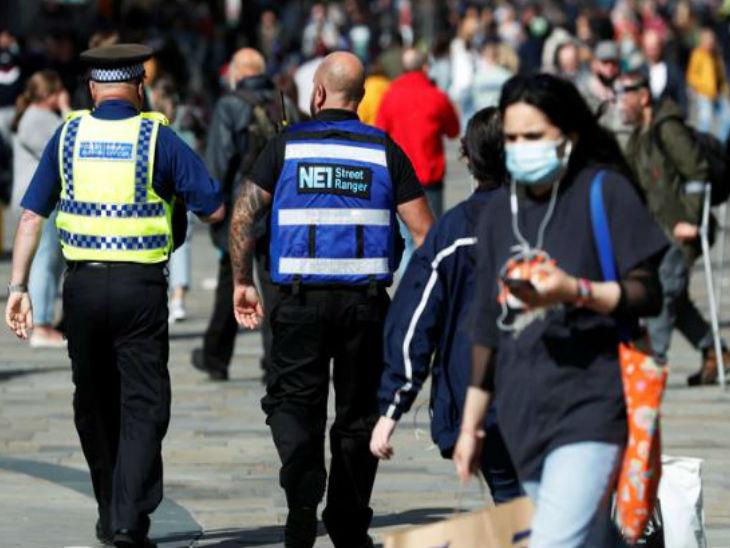 ब्रिटेन के न्यूकैसल में एक स्ट्रीट रेंजर और कम्युनिटी सपोर्ट ऑफिसर गश्त करता हुआ और मास्क लगाकर जाती एक महिला।