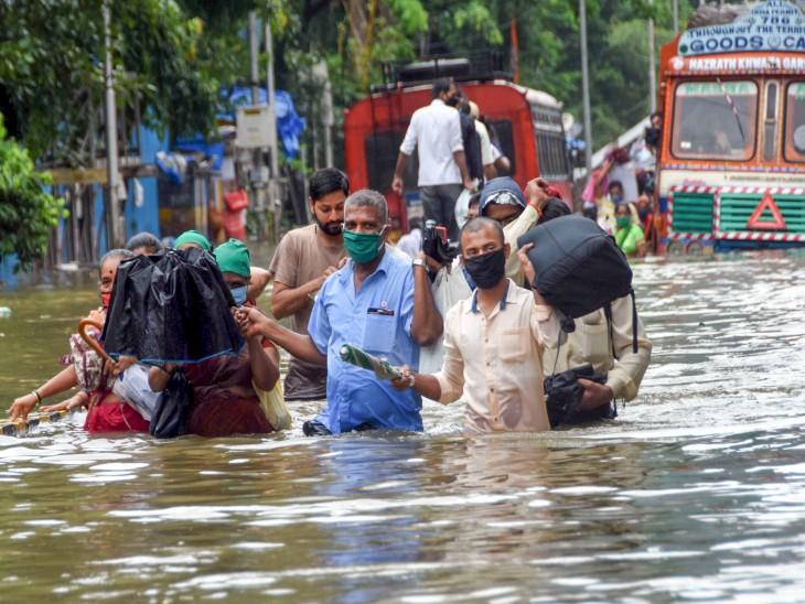 बारिश की वजह से कई लोगों को काम पर जाने में दिक्कत हुई। पानी से भरी सड़क को पार करने में लोगों ने एक-दूसरे की मदद की।