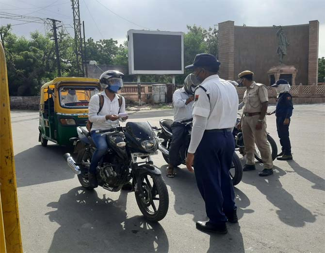 लॉक डाउन के दौरान बाहर निकले लोगों से पूछताछ करती पुलिस।