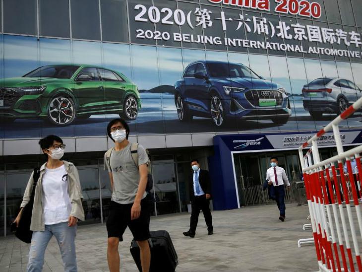 चीन की राजधानी बीजिंग में रविवार को ऑटो शो वेन्यू के बाहर से गुजरते लोग।