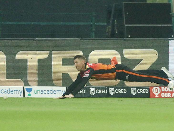 हैदराबाद के कप्तान डेविड वॉर्नर बाउंड्री पर छलांग लगाकर चौका बचाते हुए।