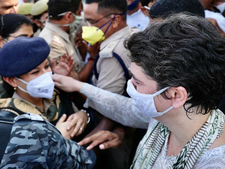 प्रियंका गांधी ने पुलिस अफसर के कंधे पर हाथ बातचीत की।
