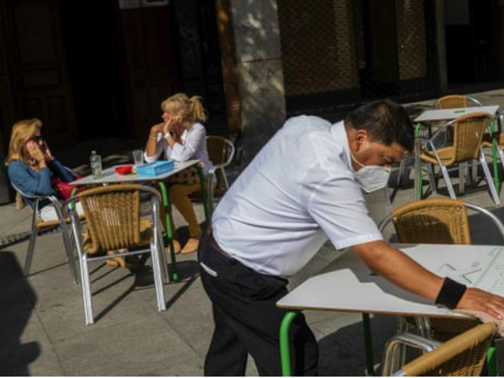 सेंट्रल मैड्रिड के एक रेस्टोरेंट में मेज सैनिटाइज करता वेटर। मैड्रिड का स्थानीय प्रशासन पहले नए प्रतिबंधों का विरोध कर रहा था। लेकिन, शुक्रवार को वह इनके लिए तैयार हो गया। (फाइल)
