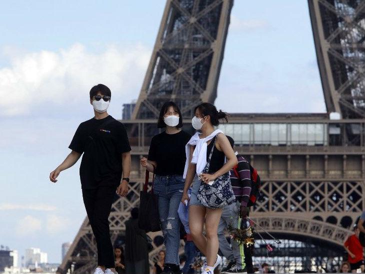 फ्रांस की राजधानी पेरिस में एफिल टावर के पास मास्क लगाकर घूमते स्थानीय लोग।