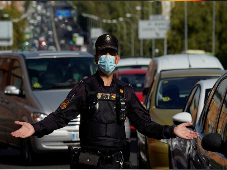 स्पेन की राजधानी मैड्रिड में शुक्रवार को इमरजेंसी के एलान के बाद ट्रैफिक सिग्नल पर मास्क लगाकर अपने काम में जुटा एक पुलिसकर्मी।