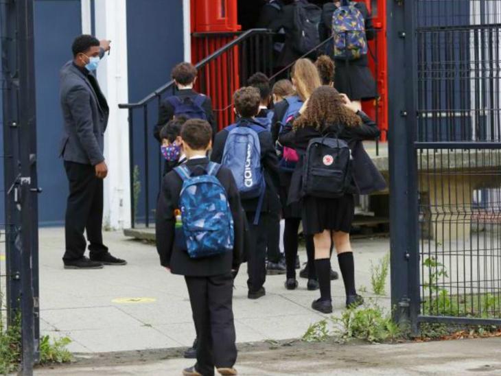 बुधवार को ब्रिटेन के एक स्कूल में जाते बच्चे। यहां एक रिसर्च में सामने आया है कि स्कूल और कॉलेज खुलने के बाद से संक्रमण में तेजी आई है।