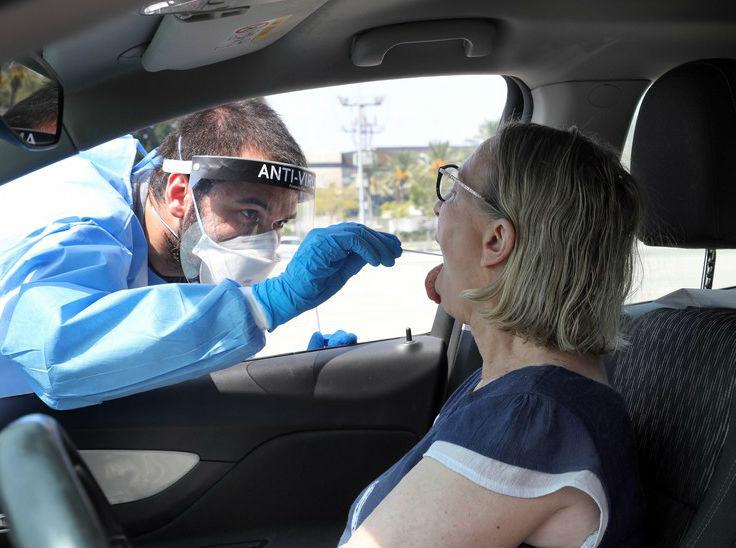 इजराइल के तेल अवीव में एक कार सवार महिला का स्वैब सैंपल लेता मेडिकल स्टाफ।